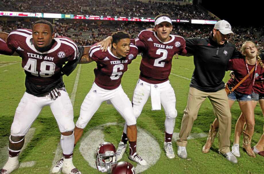 Texas A&M quarterback Johnny Manziel (2) sings the Aggie War Hymm along with defensive back Noel Ellis (6) and linebacker Darian Claiborne (48) during Saturday's game in College Station, Texas. Texas A&M won 42-13. Photo: Bob Levey — The Associated Press   / FR156786 AP