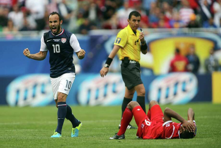 Landon Donovan (10) celebrates as Panama player Alberto Quintero (19) lies on the ground after the 2013 Gold Cup championship game at Soldier Field. USA won 1-0. (Jerry Lai-USA TODAY Sports) Photo: Jerry Lai-USA TODAY Sports / Jerry Lai