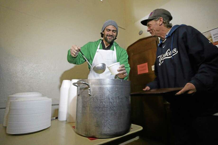 New York Jets quarterback Mark Sanchez, left, pours a bowl of soup for William Day, 52, during a visit to the Community Soup Kitchen of Morristown as part of the team's Thanksgiving Day week celebration on Tuesday in Morristown, N.J. Photo: Julio Cortez — The Associated Press   / AP