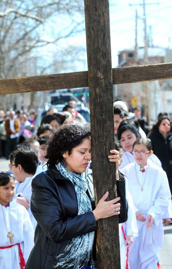 Angelina Malpica of East Haven leans on the cross after carrying it during the Stations of the Cross procession by parishioners of St. Rose of Lima Church in the Fair Haven section of New Haven on 3/29/2013.Photo by Arnold Gold/New Haven Register