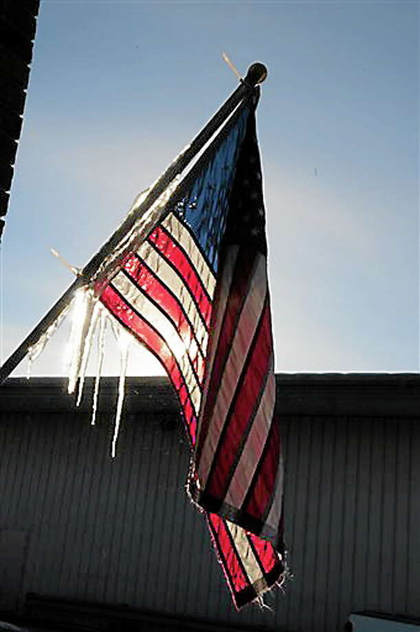 Icicles form on a U.S. flag located under melting snow on the roof of a store in Baxter, Minn. on Wednesday, Dec. 26, 2012. Cold temperatures are beginning to ease in Central Minnesota after a Christmas holiday with temperatures dipping below zero. (AP Photo/Brainerd Dispatch, Steve Kohls) Photo: AP / Brainerd Dispatch