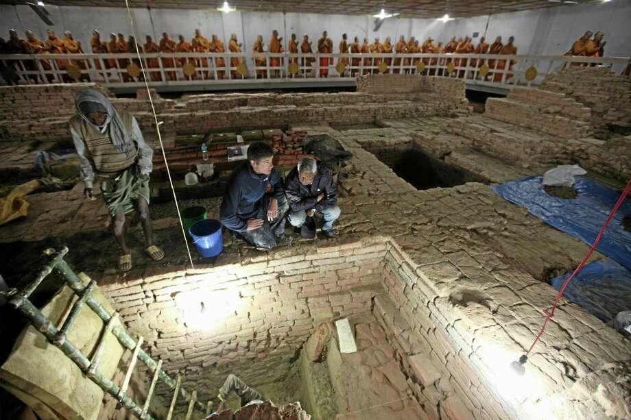 In this undated but recent photo released by National Geographic, archaeologists Robin Coningham, second from right, of Britain's Durham University and Nepalese archaeologist Kosh Prasad Acharya, right, direct excavations within the Mayadevi Temple, uncovering a series of ancient temples contemporary with the Buddha as Thai monks meditate in the background. Buddha, also known as Siddhartha Gautama, is generally thought to have been born in about the sixth century B.C. at the temple site. (AP Photo/National Geographic, Ira Block) MANDATORY CREDIT Photo: AP / National Geographic
