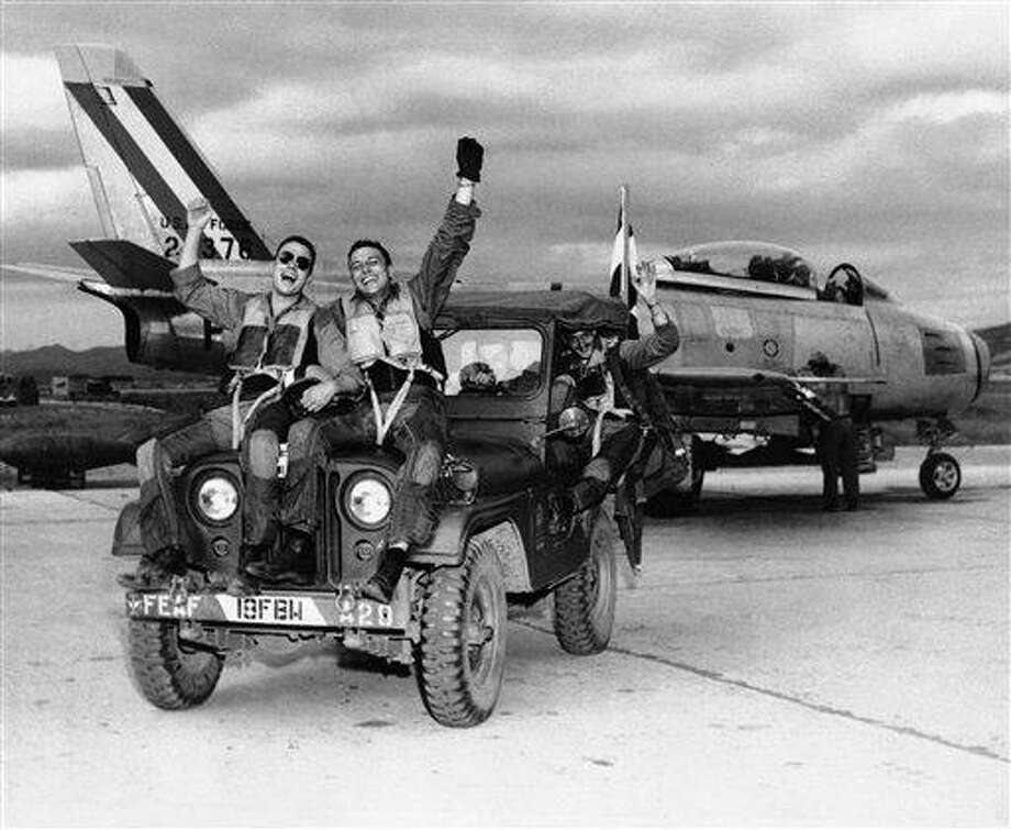 This July 29, 1953, black-and-white file photo shows happy fliers of the 18th Fighter Bomber wing. They let the world know how they feel as they come back from a  combat mission over North Korea to learn of the armistice signing. From left are: 2nd Lt. John Putty of Dallas, Tex.; 1st Lt. James A. Boucek of Ottawa, Kan.: and 1st Lt. Richard D. Westcott of Houston, Tex., waving from back seat of jeep. Sixty years after it finished fighting in Korea, the U.S. is still struggling with the political, military and human costs that war can impose on the generations that follow. America still is committed to playing a role in defending South Korea should the 1950-53 Korean War re-ignite. (AP Photo, File) Photo: AP / AP