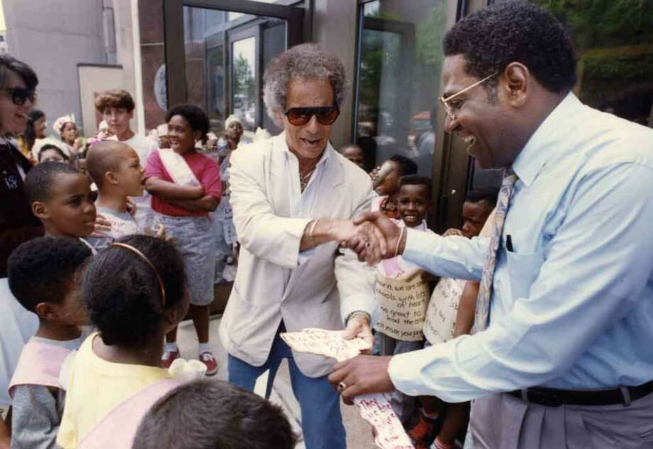 """The principal of Welch Annex School Joseph Geremia hands acting Superintendent of New Haven Schools Reginald Mayo the """"key to the city"""" to welcome him to his new job June 6, 1992. Mara Lavitt/New Haven Register"""