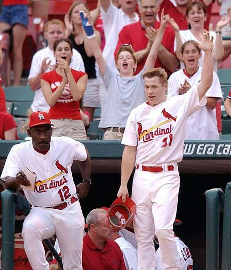 St. Louis Cardinals' Bo Hart (31) takes a curtain call as he waves to the cheering fans after hitting a solo home run in the first inning against the Cincinnati Reds Wednesday, June 25, 2003 in St. Louis. It was Hart's first home run of his major league career. Standing on the left is Mitchell Page, batting coach. (AP Photo/James A. Finley)