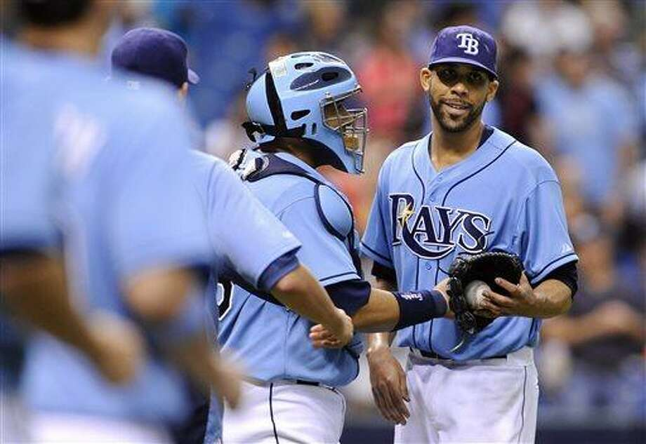 Tampa Bay Rays starting pitcher David Price, right, smiles as teammates, including catcher Jose Molina, center, come out to the mound to celebrate his complete game 3-1 win after striking out Chicago White Sox Dayan Viciedo to end a baseball game Sunday, July 7, 2013, in St. Petersburg, Fla. (AP Photo/Brian Blanco) Photo: AP / FR1707907 AP