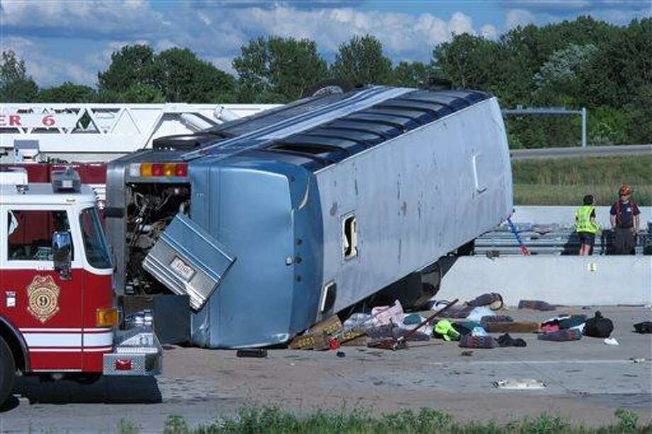 Seat cushions, clothing and other objects line the pavement next to the wreckage of bus that crashed Saturday while carrying teenagers returning from a summer camp in Michigan. Three people were killed and 26 others were taken to local hospitals following the crash, which occurred when the bus exited an interstate ramp and crashed into a concrete retaining wall. Investigators don't yet know what caused the crash about a mile from its destination, Colonial Hills Baptist Church.  (AP Photo/Rick Callahan) Photo: AP / AP