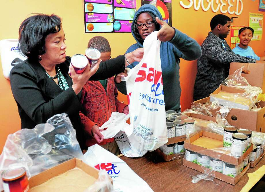New Haven Mayor-elect Toni Harp, left, and Dominique Ratchford, center, 17, of New Haven pack bags of canned food for Thanksgiving meals at Believe In Me Empowerment Corp. Tuesday. Photo: Arnold Gold — New Haven Register