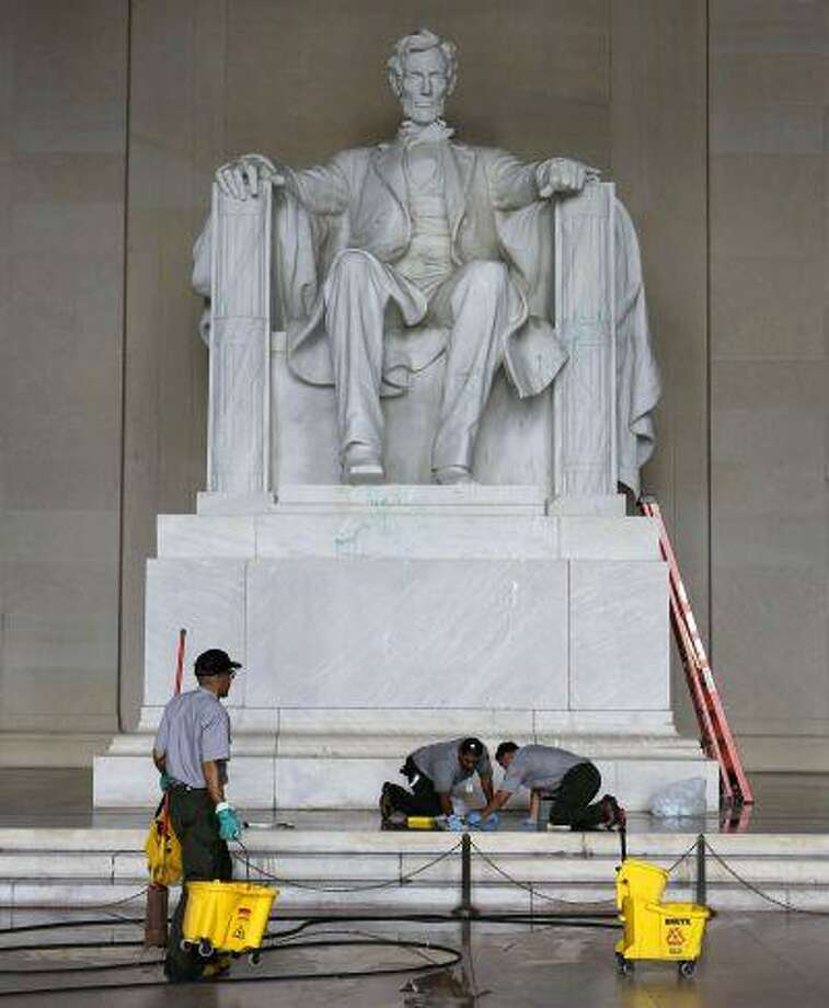 A National Park Service employee uses a pressure hose to help clean green paint from the Lincoln Memorial in Washington after it had been splattered on the statue early today which closed the popular attraction until later in the day, a U.S. Park police officer said, July 26, 2013. Photo: REUTERS / X00961