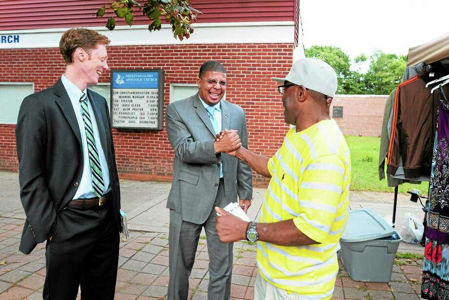 (Photo by Peter Hvizdak — Register)Kermit Carolina, center,  shakes the hand of Rodney Arnold as he campaigns for Justin Elicker, left,  while walking on Dixwell Ave. and Bassett Street in New Haven. Elicker is running in the New Haven Mayoral race against Democratic party nominee Toni Harp. Arnold, of Hamden, has a sidewalk business in New Haven and a son who goes to a New Haven school. Photo: New Haven Register / ©Peter Hvizdak /  New Haven Register