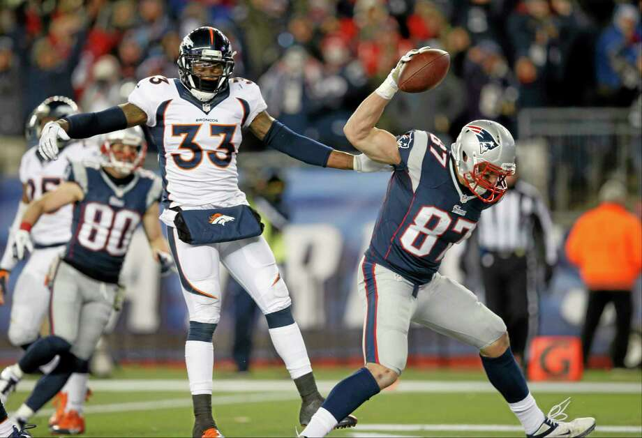 New England Patriots tight end Rob Gronkowski (87) celebrates his touchdown in front of Denver Broncos safety Duke Ihenacho (33) in the third quarter of an NFL football game Sunday, Nov. 24, 2013, in Foxborough, Mass. (AP Photo/Elise Amendola) Photo: AP / AP