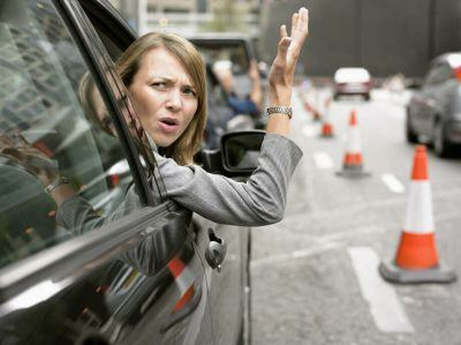Anoyed Woman Looking Out Her Car Window Gesturing Photo: Getty Images / (c) Digital Vision.