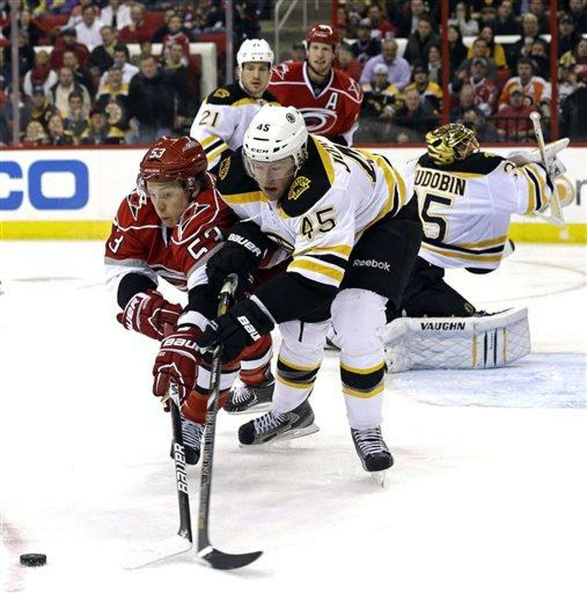 Carolina Hurricanes' Jeff Skinner (53) and Boston Bruins' Aaron Johnson (45) chase the puck during the second period of an NHL hockey game in Raleigh, N.C., Monday, Jan. 28, 2013. (AP Photo/Gerry Broome)