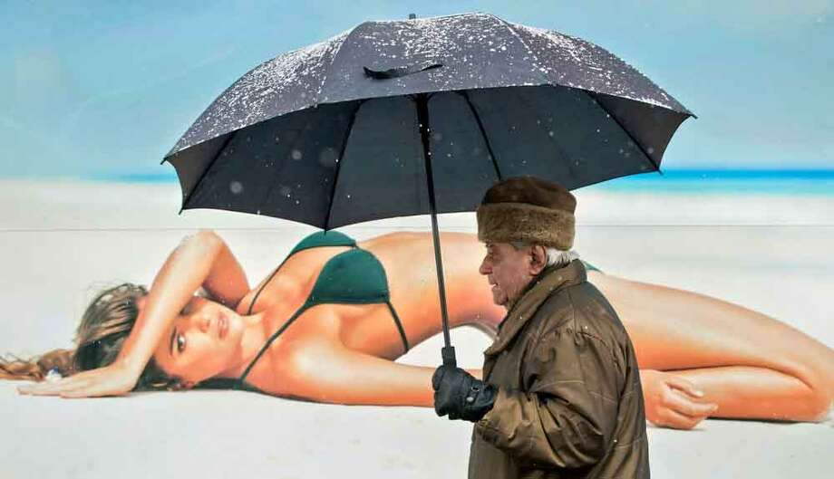 An elderly man walks holding an umbrella, during a snowfall, back dropped by a large poster in Bucharest, Romania, Monday, Jan. 28, 2013. (AP Photo/Vadim Ghirda) Photo: ASSOCIATED PRESS / AP2013
