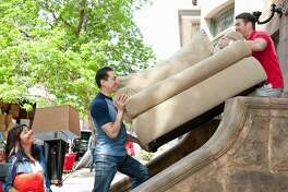two male friends carrying couch up stairs to new home, woman carrying lamp and pillow, moving truck in the background, urban environment