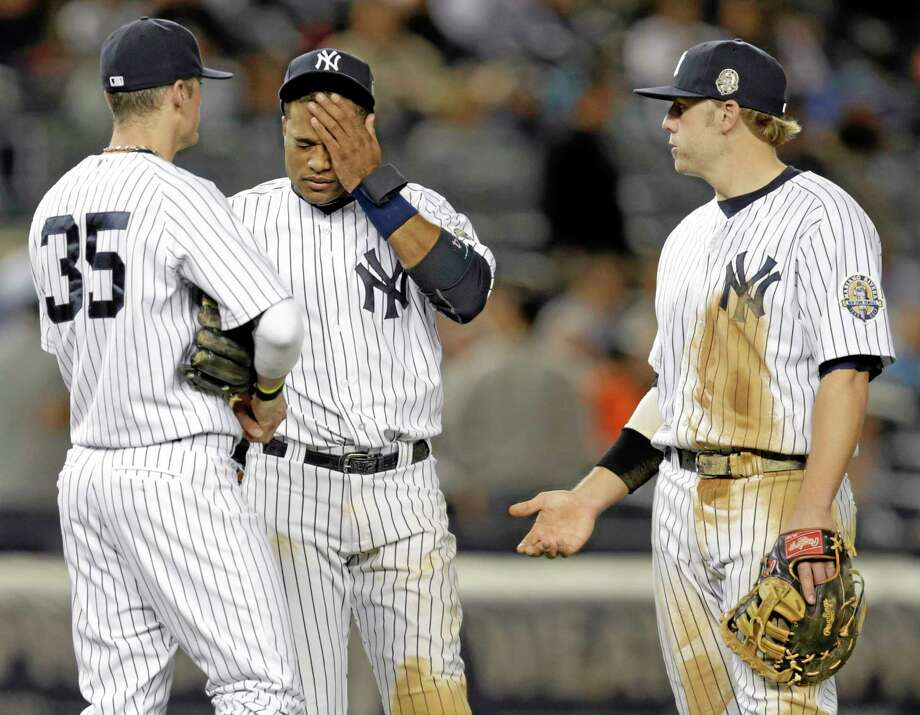 Yankees shortstop Brendan Ryan (35), second baseman Robinson Cano and first baseman Mark Reynolds wait during a pitching change after reliever David Huff gave up a sixth-inning, three-run home run to the Tampa Bay Rays' Evan Longoria on Wednesday night in New York. Photo: Kathy Willens — The Associated Press   / AP