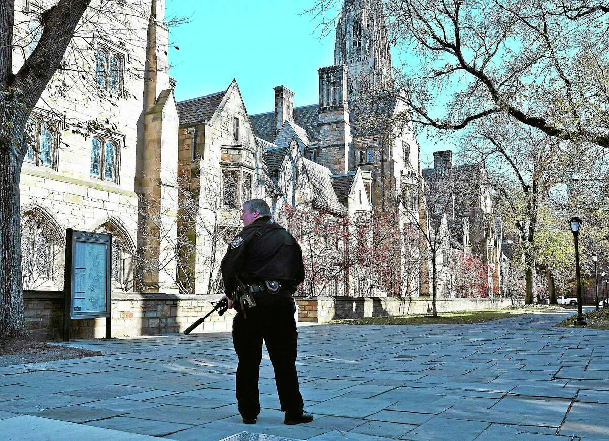 (Peter Casolino — New Haven Register) A Yale police officer keeps guard with an assault rifle on York Street during the Yale lockdown Monday Morning. pcasolino@NewHavenRegister