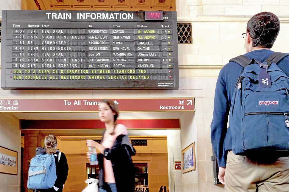 Passengers at Union Station in New Haven examine the train information board as some service is expected to be disrupted for days or longer after a 138,000-volt feeder line running from Mount Vernon to Harrison, N.Y., lost power early Wednesday. (VM Williams/Register) Photo: Journal Register Co.