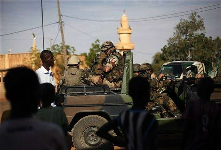 """French troops are seen  in Gao, northern Mali, Tuesday Jan. 29, 2013, days after Malian and French military forces closed in and retook the town from Islamist rebels. Earlier Tuesday, four suspected extremists were arrested after being found by a youth militia calling themselves the """"Gao Patrolmen"""". Malian soldiers prevented the mob from lynching them. (AP Photo/Jerome Delay) Photo: AP / AP"""