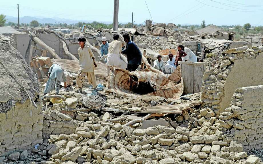 Pakistani villagers look for belongings amid the rubble of their destroyed homes following an earthquake in the remote district of Awaran, Baluchistan province, Pakistan, Wednesday, Sept. 25, 2013. Rescuers struggled Wednesday to help thousands of people injured and left homeless after their houses collapsed in a massive earthquake in southwestern Pakistan Tuesday, Sept. 24, 2013, as the death toll rose to hundreds. (AP Photo/Arshad Butt) Photo: AP / AP