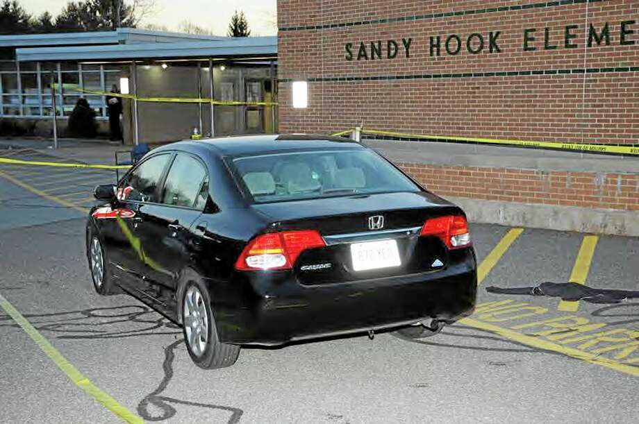 """This image contained in the """"Appendix to Report on the Shootings at Sandy Hook Elementary School and 36 Yogananda St., Newtown, Connecticut On December 14, 2012"""" and released Monday, Nov. 25, 2013, by the Danbury, Conn., State's Attorney shows a vehicle outside Sandy Hook Elementary School in Newtown, Conn. Adam Lanza opened fire inside the school killing 20 first-graders and six educators before killing himself as police arrived. (AP Photo/Office of the Connecticut State's Attorney Judicial District of Danbury) Photo: AP / Office of the Connecticut State's Attorney Judicial District of"""