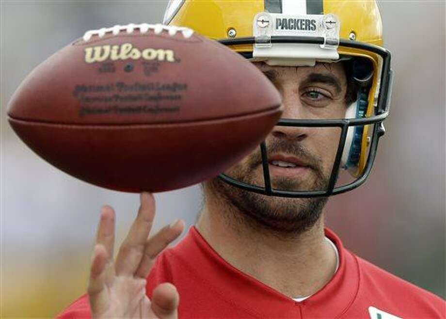 Green Bay Packers' Aaron Rodgers spins a ball on his finger during NFL football training camp Friday, July 26, 2013, in Green Bay, Wis. (AP Photo/Morry Gash) Photo: AP / AP