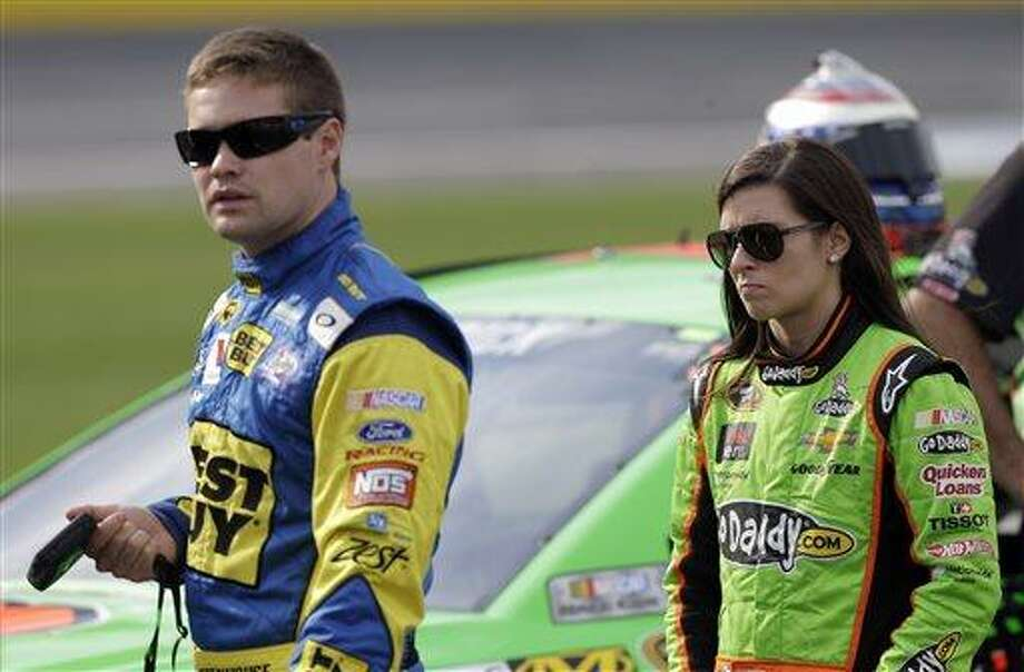 """FILE - In this May 17, 2013 file photo, Danica Patrick, right, walks with Ricky Stenhouse Jr., left, on pit road during qualifying for the NASCAR Sprint Showdown auto race at Charlotte Motor Speedway in Concord, N.C. Patrick says there were some """"silent moments"""" on the way home from Sunday's May 26, 2013 Coca-Cola 600 after Stenhouse drove his car into the side of his girlfriend's car and ended her race. It was the first run-in for the NASCAR rookies since they announced in February they were dating.  (AP Photo/Chuck Burton, File) Photo: AP / AP"""
