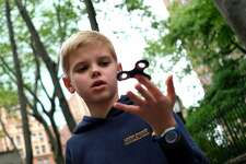 "Ten-year-old Louis Wuestenberg plays with a fidget spinner in a park in New York on May 23, 2017.  It was supposed to calm nerves, relieve stress and improve concentration but the new-anti fidget toy spreading fast through US and European schools is whipping up anger among teachers on both sides of the Atlantic. Just months after the ""fidget spinner"" first whirled its way into the hands of antsy youngsters, some schools have already banned it -- sparking a debate about difficulties children experience concentrating.  / AFP PHOTO / JEWEL SAMAD / TO GO WITH AFP STORY by Catherine TRIOMPHE, US education toys trend social        (Photo credit should read JEWEL SAMAD/AFP/Getty Images)"