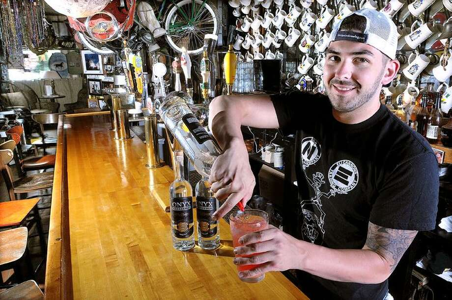 Catherine Avalone/The Middletown PressMiddletown resident Rocco LaMonica, bartender and manager at Eli Cannon's on Main Street mixes a cocktail with Onyx Moonshine which is distilled in East Hartford by two Connecticut. Onyx is the only licensed distillery. / TheMiddletownPress