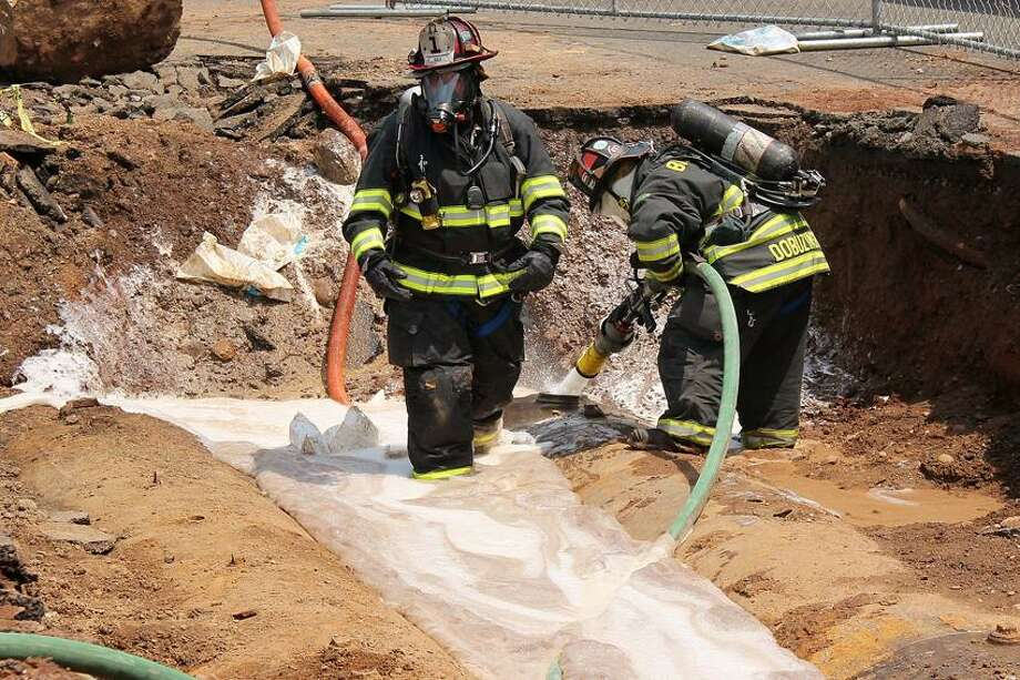 Firefighters pump foam into the area of the explosion.