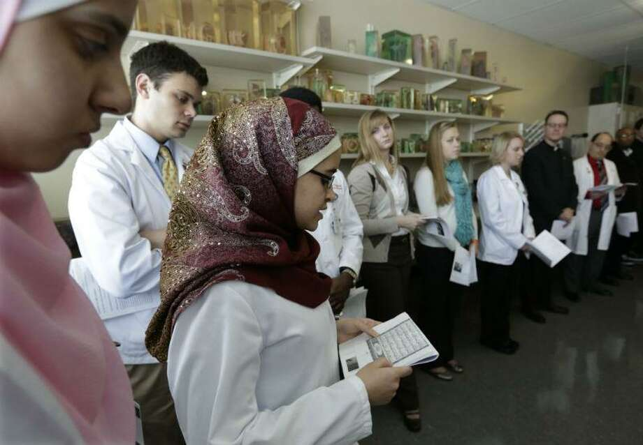 In this photo taken Friday, Jan. 25, 2013, in Gary, Ind., medical student Sarah F. Shaaban reads from the Quran during a memorial service for bodies donated to science at Indiana University School of Medicine - Northwest. During the hour long service, relatives of donors gather around the steel tables where their loved ones were dissected along with the medical students who worked on the bodies during the previous semester. The students read letters of appreciation, clergy offer prayers, and tears are shed. The program is geared towards teaching the medical students that this is not merely a cadaver, but a person, and their first patient. (AP Photo/M. Spencer Green)