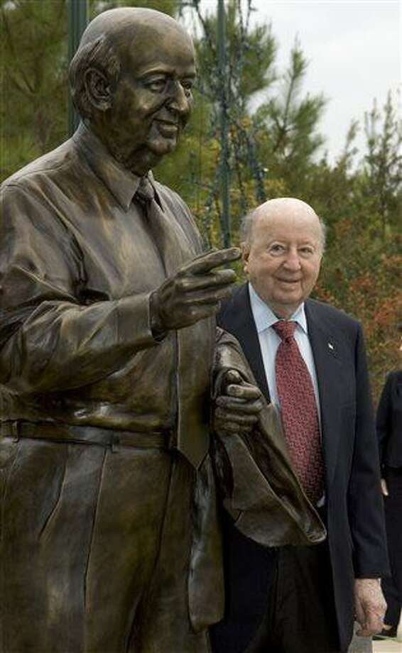 In this Nov. 8, 2007 photo, George P. Mitchell poses with a statue himself at The Woodlands at Town Green Park in The Woodlands, Texas. Mitchell, Texas oil man, real estate developer, and one of Houston's wealthiest businessmen, died Friday, July 26, 2013 at his home in Galveston, a spokeswoman said. He was 94. The oil billionaire created The Woodlands, a master-planned community  in the 1970s, north of Houston. (AP Photo/ Houston Chronicle,  Brett Coomer) Photo: AP / Houston Chronicle
