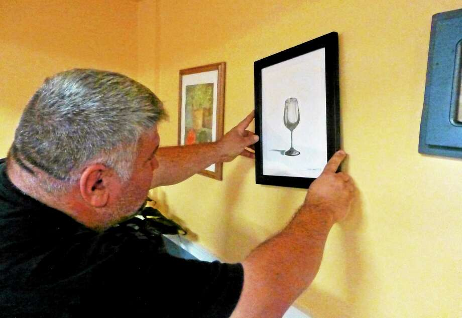 Valley Arts Council President Rich DiCarlo hangs artwork Wednesday for 'Delicious!' a food-inspirted art exhibit that opens Thursday at Marco Pizzeria in Derby. An opening reception will start at 6 p.m. (Patricia Villers/Register) Photo: Journal Register Co.