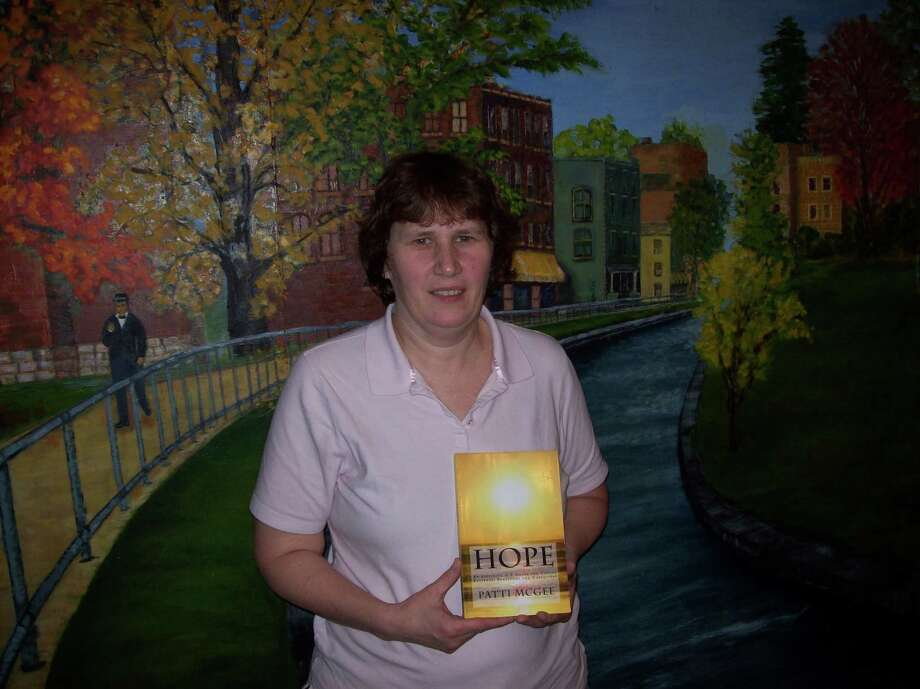 "(Photo Special to the Dispatch by MIKE JAQUAYS) Patti McGee of Oneida poses with her self-published book ""HOPE: An Inspiring A-Z Guide for Cancer Patients, Survivors and Caregivers"" on Tuesday, Jan. 29, 2013. She has taken her own experiences following her diagnosis with breast cancer in 2002 to help other cancer patients going through their own treatments and recovery."