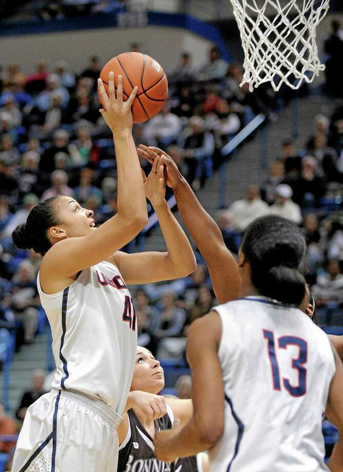 UConn's Kiah Stokes (41) scores two of her 19 points as teammate Brianna Banks (13) and St. Bonaventure's Kelcie Rombach, center, stand by during the first half Sunday. Photo: Fred Beckham — The Associated Press   / FR153656 AP