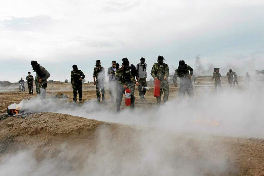 In this picture released by Tasnim News Agency on Wednesday, Nov. 20, 2013, members of Iran's paramilitary Basij force, which is controlled by the Revolutionary Guard, attend a maneuver of preparation for possible attack on Iran's nuclear sites, by the nuclear power plant in Bushehr, southern Iran. (AP Photo/Tasnim, Hosein Heydarpour) Photo: AP / Tasnim News Agency