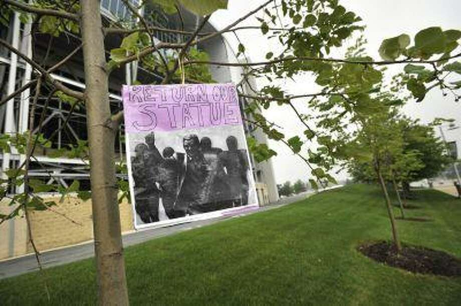 "A sign reading ""Return our statue"" hangs from a tree at the site where former Penn State college football coach Joe Paterno's statue once stood in State College, Pa. on Monday, July 22, 2013. It marks the one-year anniversary of the date it was removed in the aftermath of the Jerry Sandusky child sex abuse scandal. Photo: AP / Centre Daily Times"
