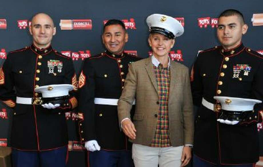 """From left, Gunnery Sergeant Phillip Campo, Staff Sergeant Victor Pozo, Ellen DeGeneres, Sergeant Antonio Sanchezattend the Ellen DeGeneres officially launches the Duracell """"Power a Smile"""" Program, on Friday, Nov. 22, 2013, at Van Nuys Airport in Los Angeles."""