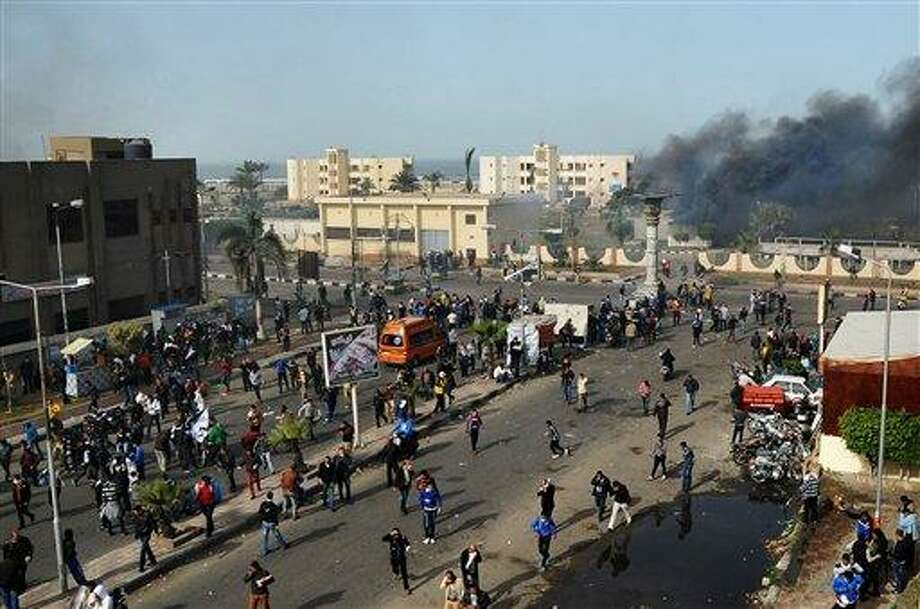 FILE - In this Sunday, Jan. 27, 2013 file photo, Egyptian protesters clash with police, unseen, in Port Said, Egypt, Sunday, Jan. 27, 2013. Thousands of mourners chanting for the downfall of Egypt's president marched in funerals again Tuesday in the restive city of Port Said as the army chief warned the state could collapse if the latest political crisis drags on. (AP Photo, File) Photo: AP / AP