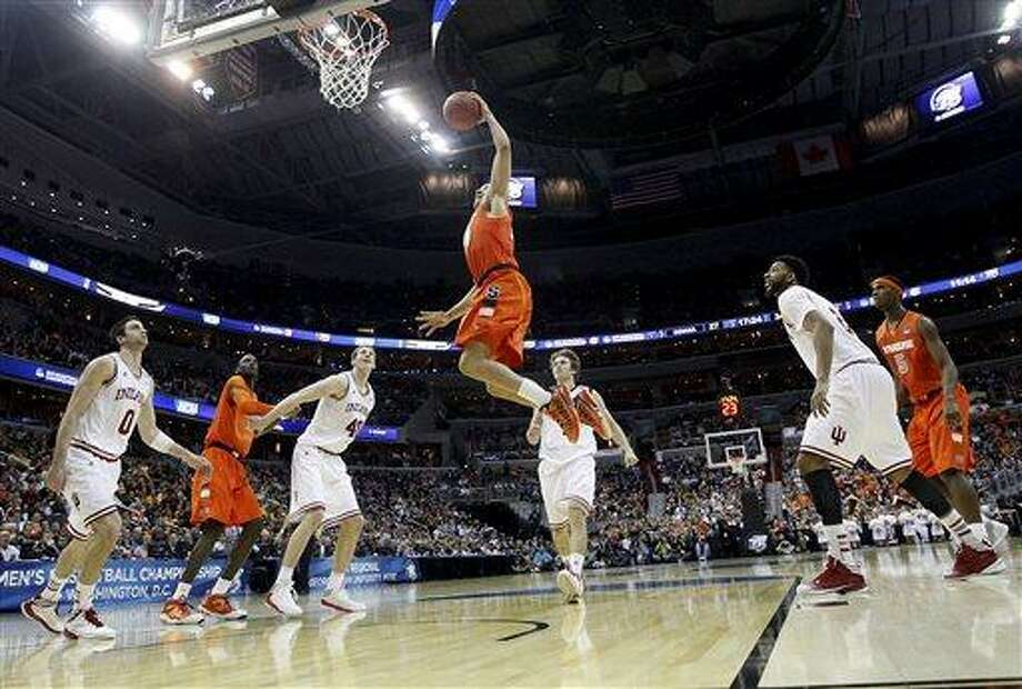 Syracuse guard Brandon Triche (20) elevates toward the basket as Indiana forwards Will Sheehey (0) and Cody Zeller (40) watch during the second half of an East Regional semifinal in the NCAA college basketball tournament, Thursday, March 28, 2013, in Washington. (AP Photo/Pablo Martinez Monsivais) Photo: AP / AP