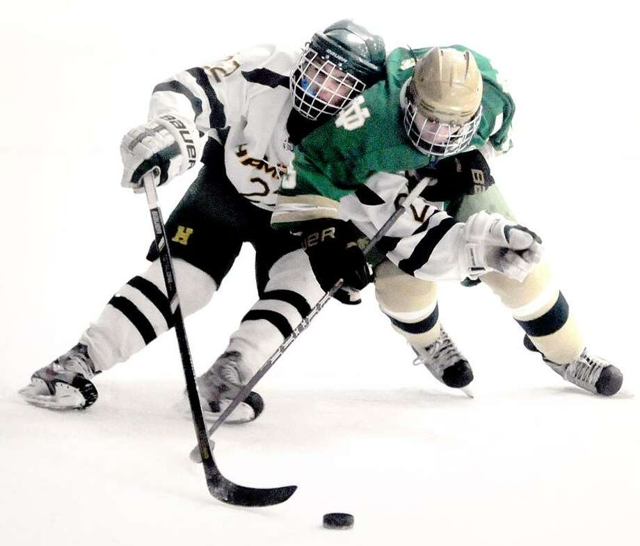 Michael DeMatteis (left) of Hamden and Cameron Hotchkiss (right) of Notre Dame of West Haven fight for the puck in the first period on 1/26/2013.Photo by Arnold Gold/New Haven Register