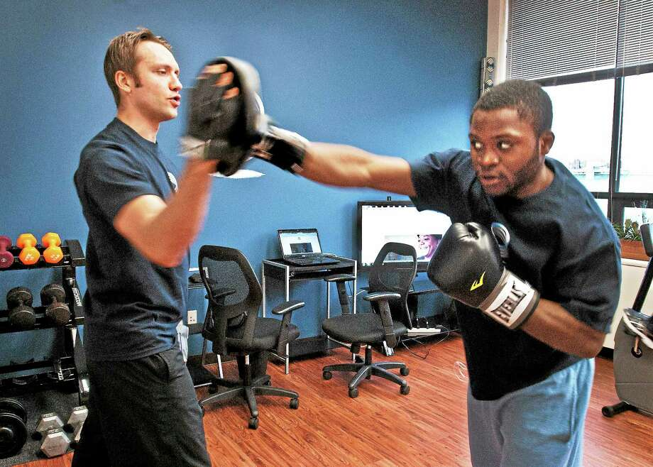 Charlie O'Connell of New Haven works out with Harding High School student Rayquon Davis. Photo: Melanie Stengel — New Haven Register