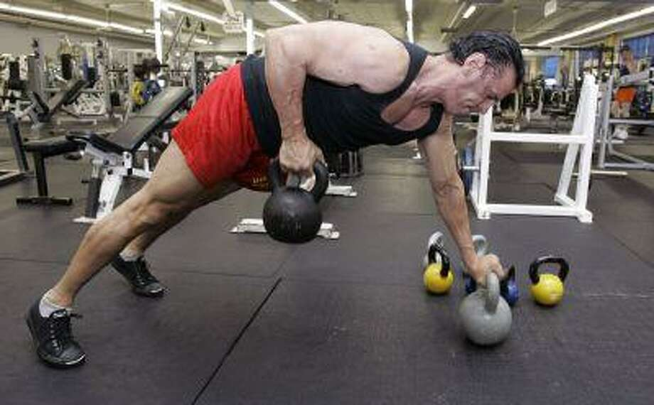 Bob Bonham, owner of Strong and Shapely Gym, works out with kettlebells at his gym in East Rutherford, N.J., Tuesday, Sept. 16, 2008. Kettlebells, a centuries-old Russian training tool, is becoming the hot new workout, as a growing number of men and women turn to the cannonball with a handle to help them shed pounds and build muscle. (AP Photo/Mike Derer) Photo: ASSOCIATED PRESS / AP2008