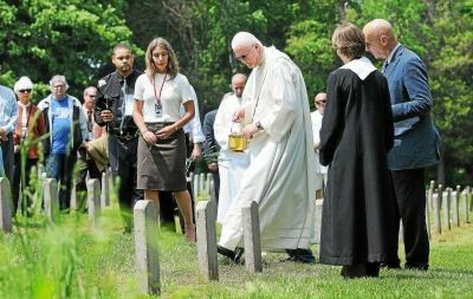 Catherine Avalone/The Middletown Press Deacon Peter Gill of St. Coleman Parish in Middlefield blesses a gravesite of a patient during the fifteenth year of the continuing ceremony recognizing people buried in the Connecticut Valley Hospital cemetery on Silvermine Road between 1878 and 1955. / TheMiddletownPress