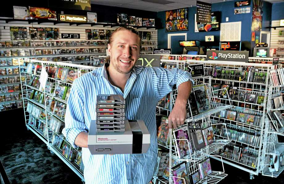 (Peter Casolino — New Haven Register) Kris Krohn, owner of the newly opened Retro Games Plus store in Orange that specializes in vintage video games and systems. They also sell new and used new items. 09/23/13 Photo: Journal Register Co.