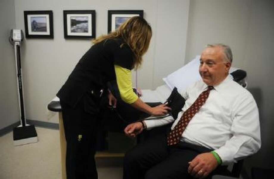 Lisa Trever takes the blood pressure of AlloSource CEO Tom Cycyota at the firm's on-site health clinic.