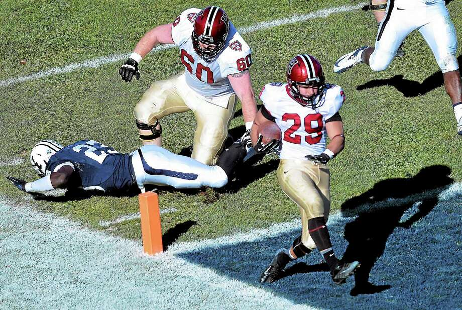 Harvard's Paul Stanton runs in for the second of his four touchdowns on the day as Yale's Foyesade Oluokun just misses the diving tackle during the first quarter of the Crimson's 34-7 win over Yale on Saturday afternoon in the 130th edition of The Game at the Yale Bowl. Photo: Peter Casolino — Register