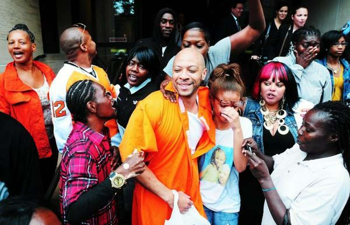Sean Adams (center) hugging his daughter, Ashante, 16, is surrounded by friends and family as he leaves Superior Court in New Haven after his release from prison on 7/25/2013. Arnold Gold/New Haven Register