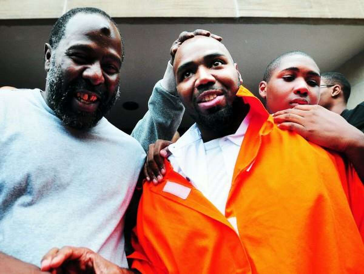 Darcus Henry (center) is hugged by his son, Darcus, Jr. (right), 14, as he leaves Superior Court in New Haven after his release from prison on 7/25/2013. Arnold Gold/New Haven Register