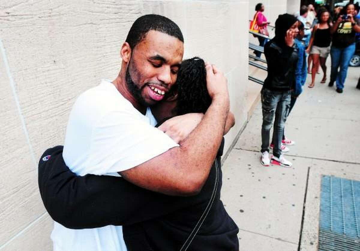 Carlos Ashe (center) is hugged by an aunt outside of Superior Court in New Haven after his release from prison on 7/25/2013. Arnold Gold/New Haven Register